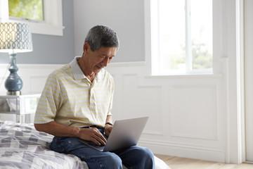 Senior Man Sitting On Bed Using Laptop Computer
