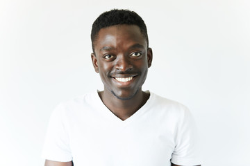 Portrait of handsome young African black male wearing white T-shirt looking and smiling at the camera with cheerful and happy expression, relaxing indoor against white studio wall background