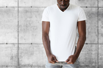T-shirt design and advertising concept. Cropped studio portrait of dark skinned young male posing against white copy space wall wearing white T-shirt with copy space for your advertising content