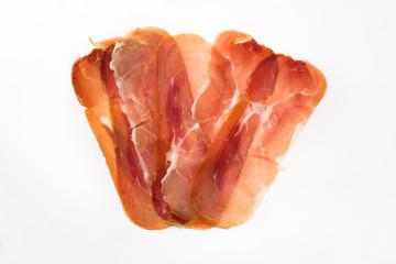 Thin slices of spanish serrano ham isolated on white background