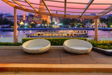 Relax corner on condominium rooftop garden with chairs on landmark bangkok Wat Arun and cruise ship in night background, Landmark concept