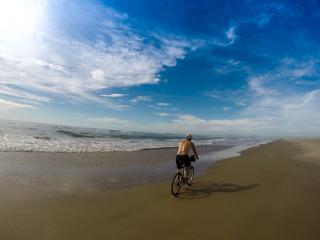 Homem andando de bicicleta na praia durante o dia