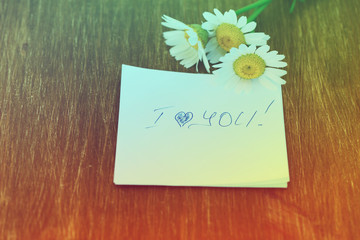 """Daisy flower and piece of paper with text """"I love you"""" on the wooden table. Photo in vintage style"""