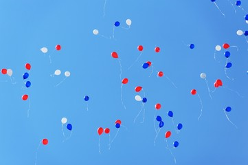 White, blue and red baloons flying high in clear blue sky