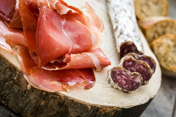 Spanish serrano ham, olives and sausages on a tree trunk
