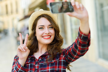 Young woman selfie in the street with a smartphone