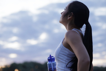 Woman jogger drinking water from shaker after workout training