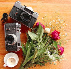 vintage camera near a bouquet of flowers and candles