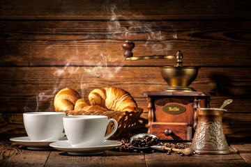 Coffee and croissants on wooden background