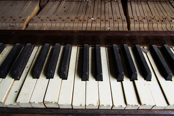 Old broken disused piano with damaged keys