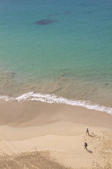 View of people walking along the beach's seashore with a turquoise water in Fernando de Noronha, Brazil, on a sunny day