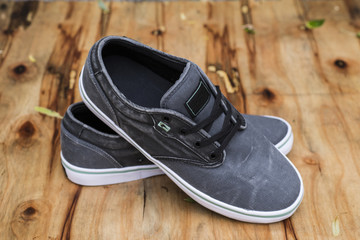 men's gray sneakers on wooden background. outdoor