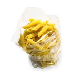 raw italian pasta penne in a transparent plastic bag from above, isolated on a white background