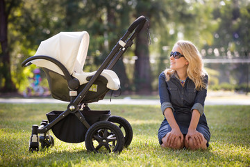 Young woman with her newborn baby enjoying sunny summer day in the park. Mother with child in the stroller outdoors. Motherhood.  Mum with baby walking in the city.