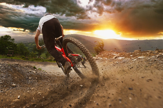 Man on mountain bike rides on the trail on a stormy sunset.
