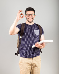 Student with book showing OK sign