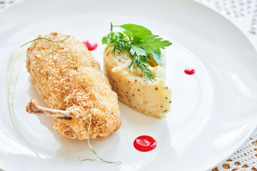 Chicken Kiev fried in breadcrumbs, Parmesan sauce and mashed potatoes with Dijon mustard served on a white plate