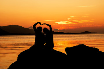 Silhouette of young couple in love at beach,sunset background