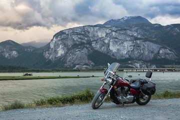 Cruser motorcycle on a dirt road with a moutainous background (Chief Mountain). Taken in Squamish, BC, Canada