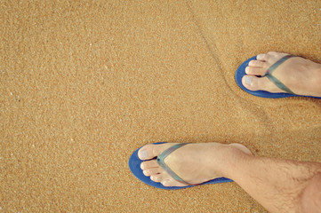 Top view close up of man wearing blue flip flops walking along tropical exotic ocean beach