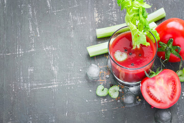 Tomato juice in glass, tomatoes and celery, top view, copy space