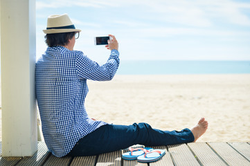 Rear side view of a man with smartphone sitting on a beach terrace on a sunny day outside