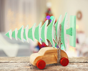 Wooden toy car carrying Christmas miniature  tree on shiny lights background