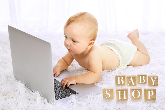 Cute baby boy with laptop on carpet in room. Baby shop concept