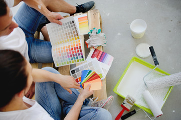 Two persons choose color of a decor, having inclined over catalogs.