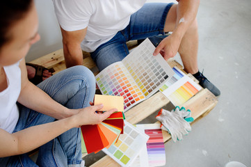 Two persons choose color of decor, sitting on the wooden pallet at a cement floor.