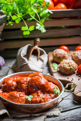 Tasty meatballs with tomato sauce and parsley