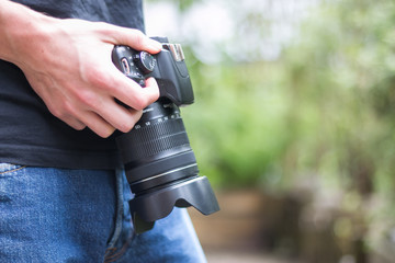 Junger Mann hält Spiegelreflexkamera in der Hand, Hüftperspektive