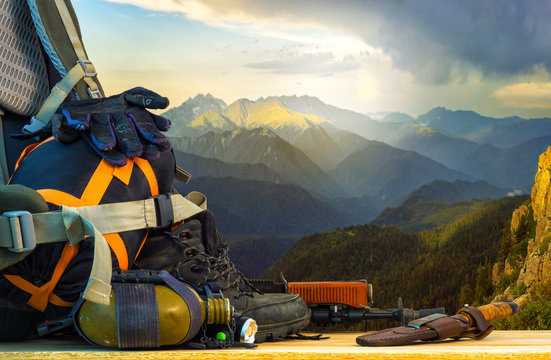 Backpack traveler and travel gear, on the background of mountain