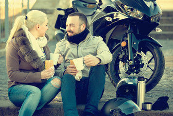 adults chatting near motorcycle