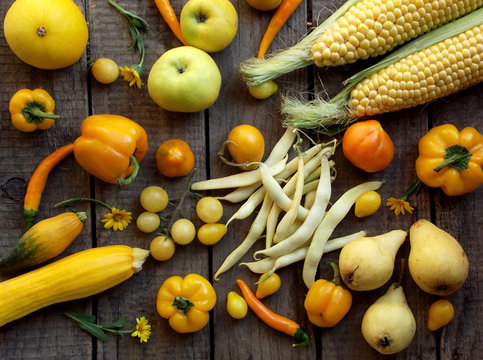 yellow fruits and vegetables on a wooden background