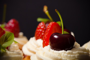 Fresh cupcakes with cream and berries. Shallow depth of field. S