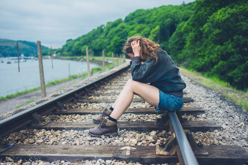 Sad young woman sitting on railroad tracks
