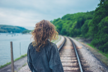 Young woman walking on railroad tracks