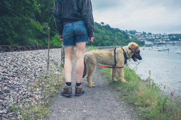 Young woman walking dog by railroad tracks