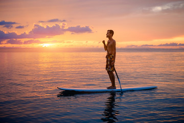 Silhouette of man paddleboarding at sunset