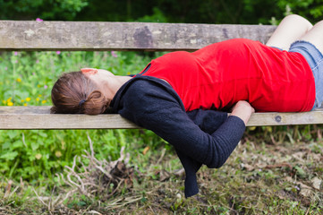 Pregnant woman sleeping on bench in forest