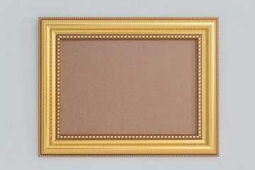 Antique golden frame isolated on white wall