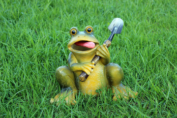 Frog with a shovel on a background of grass