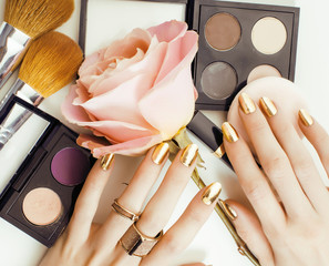 woman hands with golden manicure and many rings holding brushes, makeup artist stuff stylish, pure close up pink flower rose among cosmetic