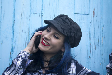 hipster girl talking on mobile phone on blue background