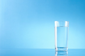 glass of pure water on a blue background