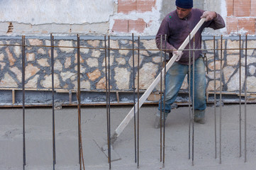 Workers with rake leveled the concrete