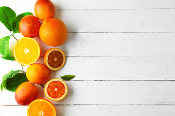 Different kinds of oranges on white wooden table
