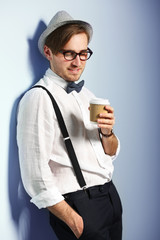 Young handsome man with a cup of coffee on light blue background
