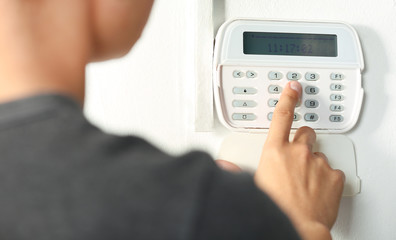 Man pressing the code on a house alarm - fototapety na wymiar